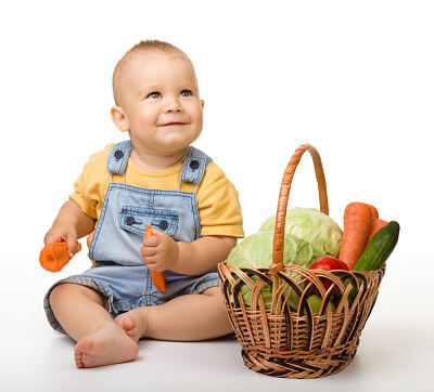 Baby with vegetables, ready to enjoy some vegetarian baby food recipes